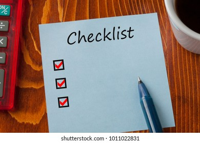 Checklist written in note with pen, calculator and cup of coffee on wooden desk. Top view.