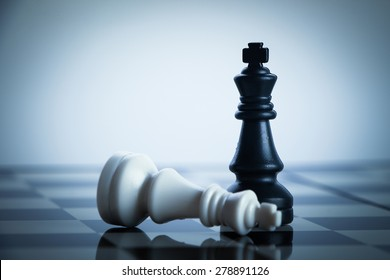 Checkmate black chess defeats white king on the chess board.
