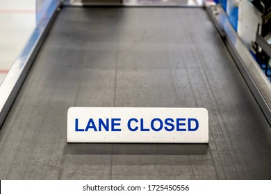Checkout lane conveyor belt at grocery store has a sign saying it is closed