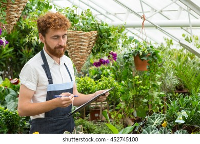Checkup time. Small business owner male florist checking the stock in his garden center
