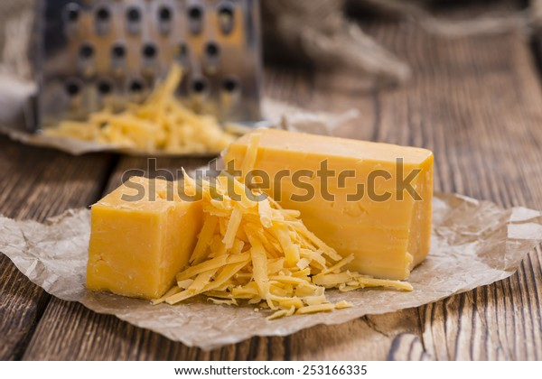 Cheddar Cheese (grated) as close-up shot on an old vintage wooden table