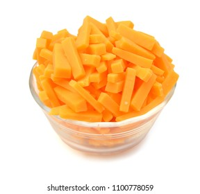 Cheddar cheese slices in glass bowl on white background.