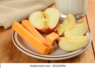 Cheddar cheese sticks with a sliced apple and milk