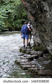 Chee Dale, England, 3rd August 2019. A man and a woman negotiating the slippy limestone stepping stones in the swollen river at Chee Dale near Buxton, in The Peak District National Park England.
