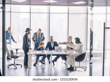 Cheeful multiracial group of businessmen having fun during meeting in office room, excited male employees laughing enjoying funny jokes at work break.