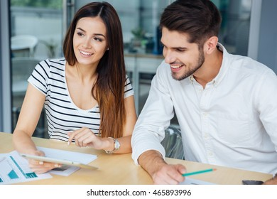 Cheeful young man and woman using tablet and working in office