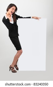 Cheeky young woman in skirt suit with blank board