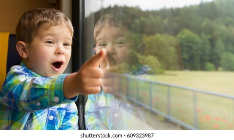 Cheerful 3 years old boy standing by a train window and pointing outside /It' s huge, look from the window!