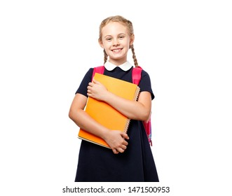 Cheerful 8 years old schoolgirl with backpack wearing uniform standing isolated over white background. Ready for school