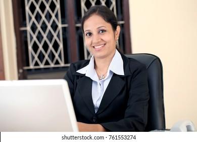 Cheerful active businesswoman at desk