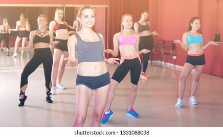 Cheerful active females funk jazz dancers exercising dance moves in studio