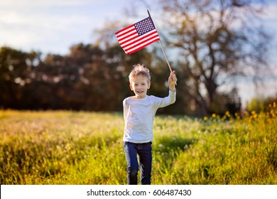 cheerful active little boy running and waving american flag celebrating 4th of july