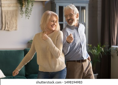 Cheerful active middle-aged mature husband and wife have fun in living room together moving to rhythm, happy overjoyed senior spouses or couple dance enjoy leisure weekend activity relaxing at home