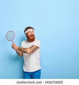 Cheerful active player focused happily into distance, holds racket and plays badminton, has attentive look, ready to serve, dressed casually, stands alone against blue studio wall with empty space