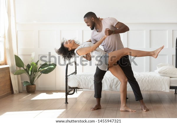 Cheerful active romantic african american couple wearing pajamas dancing in bedroom together, happy carefree young black husband and wife enjoy weekend morning laughing bonding having fun at home