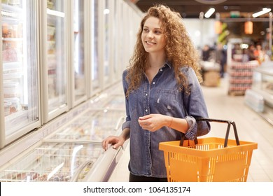 Cheerful adorable curly woman in denim jacket, holds shopping basket, strolls in supermarket, being in good mood. Pretty female comes at grocer`s shop to buy necessary products