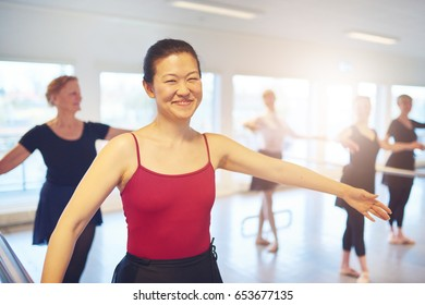 Cheerful adult Asian female ballet performer looking at camera and smiling while doing gymnastics.