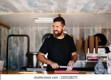 Cheerful adult cook in apron preparing meat while working as chef of food truck smiling away