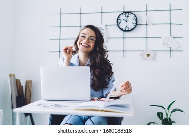 Cheerful adult dark haired woman in casual clothes and glasses looking at camera while sitting at desk and rising hand against white wall with black decor and clock in light minimalistic apartment