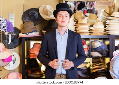 Cheerful adult male shopping in botique and try on top hat