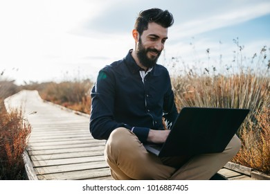 Cheerful adult man chilling on pier in dry grass using portable laptop in sunlight.