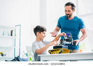 Cheerful adult man holding a robotic device while helping his son with engineering project
