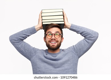 Cheerful adult man with stack of books on head on white background.