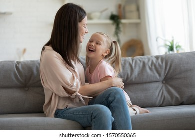 Cheerful adult mom playing laughing with little kid daughter on sofa, playful young parent mother having fun with pretty cute child girl enjoying laughter funny family lifestyle relaxing sit on couch
