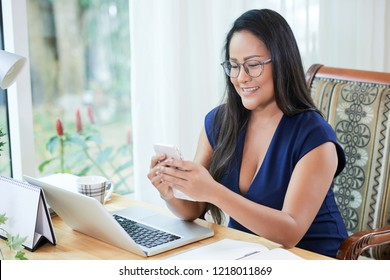 Cheerful adult Thai businesswoman in glasses using phone sitting at working desk with laptop