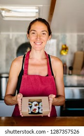 Cheerful adult woman in red apron giving box of delicious sushi working in street food truck