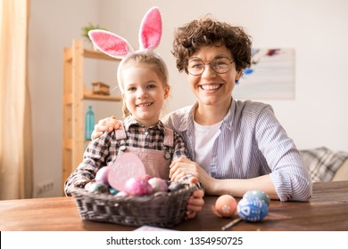 Cheerful affectionate daughter and mother looking at you while congratulating on Easter holiday