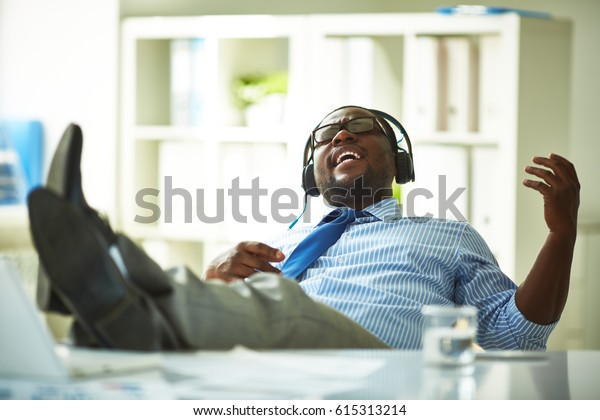 Cheerful African American businessman listening to music in headphones with closed eyes, gesticulating and sitting on chair with legs on table