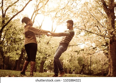 Cheerful African American couple holding hands and rotate in circle in forest.