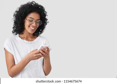 Cheerful African American with crisp hair, holds modern smart phone, happy to recieve message, dressed in casual t shirt, poses against white background with blank space for your advertisement