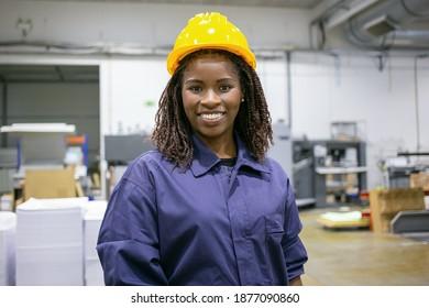 Fröhliche afroamerikanische Fabrikangestellte im harten und allgemeinen Zustand auf dem Pflanzenboden, Kamera und Lächeln. Vorderansicht, mittlere Aufnahme. Konzept der Frauen in der Industrie