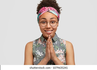 Cheerful African American female model keeps hands together in praying gesture, expresses hope and please, has some request, poses against white background. Dark skinned woman asks for forgiveness