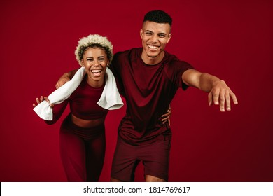 Cheerful african american fitness couple relaxing and having fun after workout. Happy couple holding each other and bending forward against maroon background.