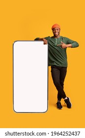 Cheerful African American Guy Leaning And Pointing At Big Smartphone With White Blank Screen, Showing Free Copy Space For Your Mobile App Or Website Design, Standing On Yellow Background, Mockup Image