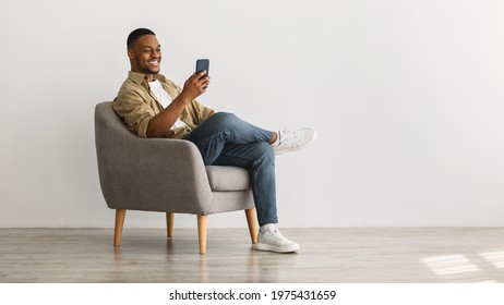 Cheerful African American Guy Using Mobile Phone With New Application Sitting In Armchair Over Gray Wall Background. Gadgets And Mobile Communication Concept. Panorama, Empty Space For Text