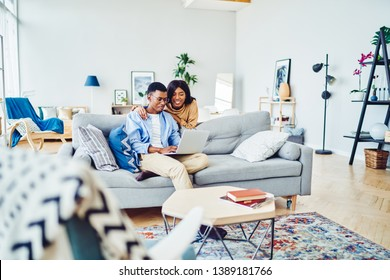 Cheerful african american hipster girl making shopping with her boyfriend via laptop computer spending time at apartment, positive couple in love watching video on netbook resting in living room
