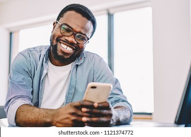 Cheerful african american hipster guy laughing at funny video on smartphone during free time, happy dark skinned man enjoying good connection of 4G internet for watching movie on mobile phone