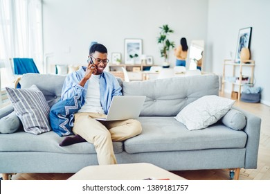 Cheerful african american hipster guy having mobile phone talk while working remotely from home on netbook, smiling male freelancer calling to banking service making transaction on laptop computer