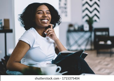 Cheerful African American housewife sitting in own apartment with fresh issue of fashion magazine and smiling during weekend, dark skinned woman holding glossy journal and laughing at home interior