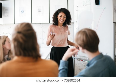 Cheerful African American lady with dark curly hair standing near board and happily looking at her colleagues in office. Young beautiful business woman giving presentation to coworkers during meeting