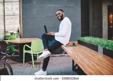 Cheerful african american male freelancer working on distance job on coworking terrace, happy dark skinned hipster guy in trendy spectacles updating antivirus system on netbook to be safe in network