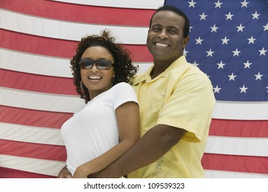 Cheerful African American man embracing woman from behind in front of an American flag