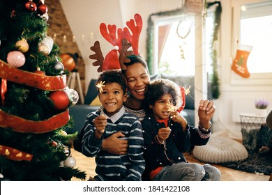 Cheerful African American mother and her kids using sparklers and having fun on Christmas.