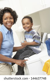Cheerful African American mother and son in the laundry room