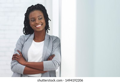 Cheerful African American Office Girl Smiling At Camera Crossing Hands Next To Wall In Office. Empty Space For Text