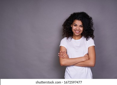 A cheerful African American with a pleasant smile, curly dark hair, healthy skin, wears a white T-shirt, stands on a gray background, being in a good mood, crossed her arms over her chest.